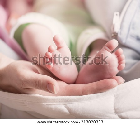 Baby feet in mother hand - stock photo