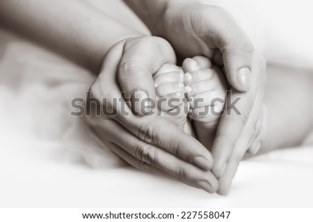 Baby feet in mother's hands. Mother's hands carefully keeping baby's foot with tenderness - stock photo