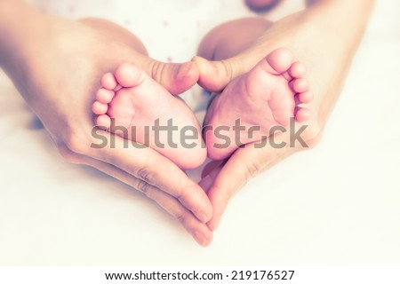 Baby feet in the mother hands - stock photo