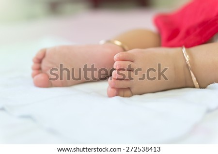 Baby feet on the bed - stock photo