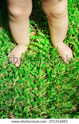 baby feet on the green grass. - stock photo