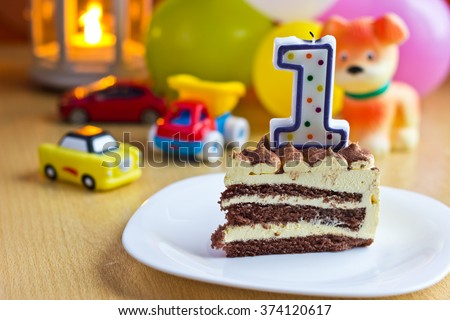 Baby first birthday party. Focus on cake with candle. Blurred multicolored background - stock photo