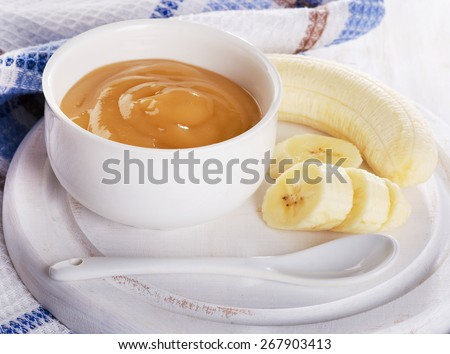 Baby food - bananas puree in a white bowl. Selective focus - stock photo