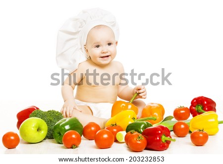 Baby food. Child in cook hat sitting inside vegetable over white background. Healthy meal concept.  - stock photo