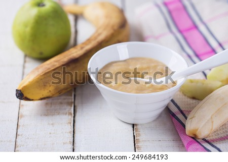 Baby food from banana and apple on wooden background. Selective focus. - stock photo