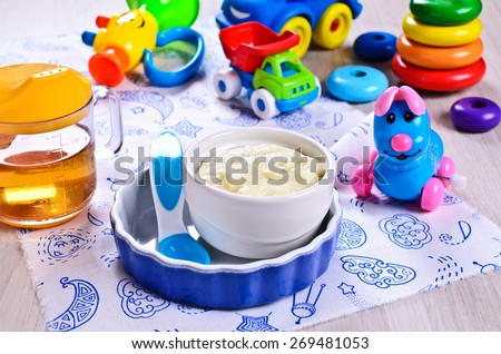 Baby food on the plate on the background of children's toys - stock photo