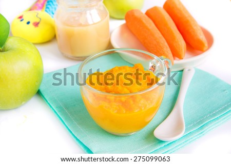 Baby food (pureed carrot and apple) close up on white table - stock photo
