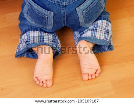 Baby foots close-up on the  wooden floor - stock photo