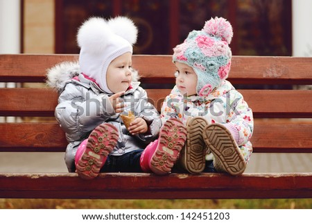 baby friends sitting  on the bench - stock photo