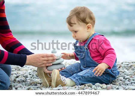 Baby girl and her mother playing with pebbles on the beach - stock photo