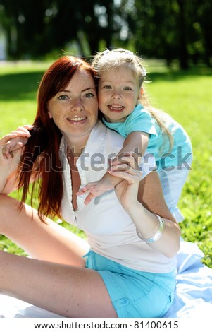 Baby girl and mother in the park - stock photo