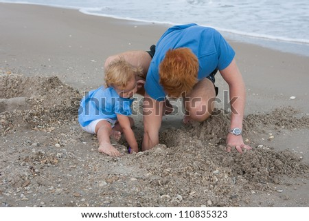Baby girl and teenage boy digging in the sand at the beach - stock photo