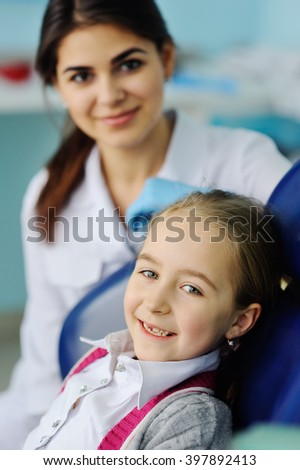 baby girl at the dentist. little girl smiling with no teeth in the dental chair - stock photo