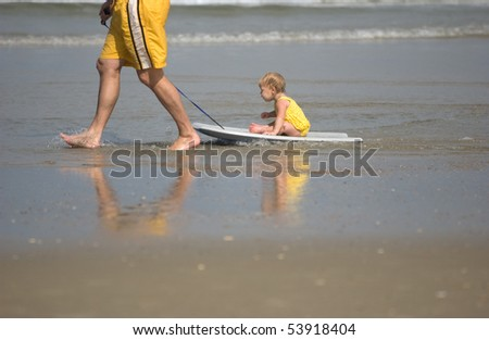 Baby girl being pulled by her dad at the beach riding a boogie board - stock photo