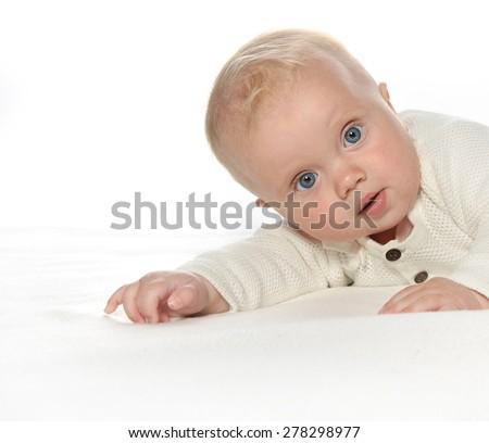 baby girl child lying down on white blanket fashion portrait face studio shot isolated on white caucasian - stock photo