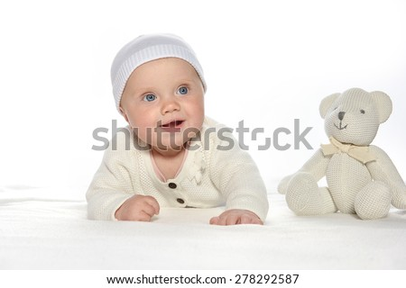 baby girl child lying down on white blanket smiling happy white clothing fashion portrait face studio shot isolated on white caucasian teddy bear - stock photo