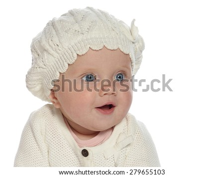 baby girl child sitting down on white blanket smiling happy in white warm clothing hat fashion portrait face studio shot isolated on white caucasian - stock photo