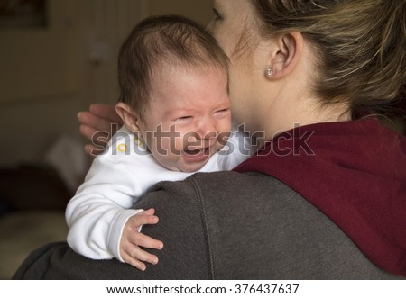 baby girl crying on mums shoulder - stock photo
