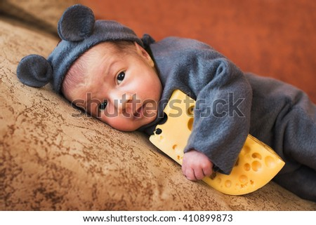 baby girl dressed as a mouse with piece of cheese - stock photo
