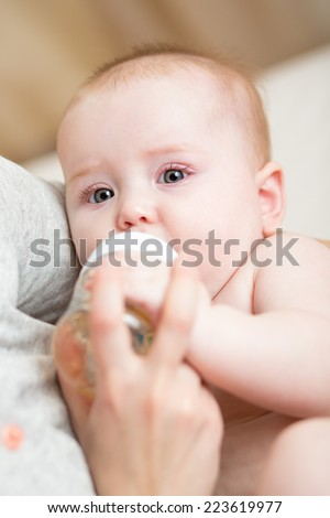 baby girl drinking water from bottle - stock photo