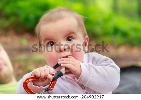 Baby girl eating climbing equipment quickdraw  - stock photo