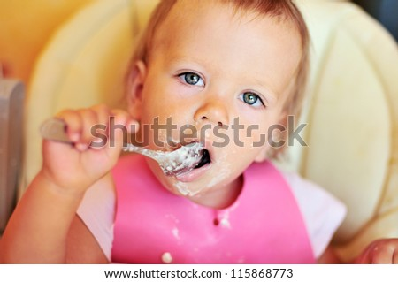 baby girl eating on her own with big spoon - stock photo