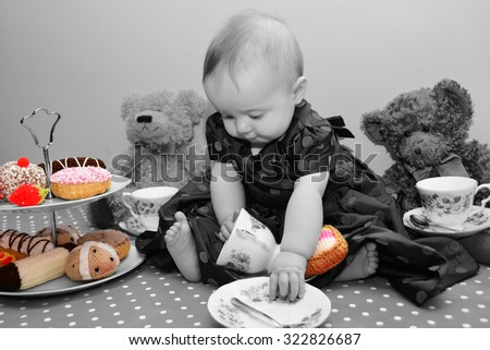 Baby girl having a tea party with her cuddly toys - stock photo