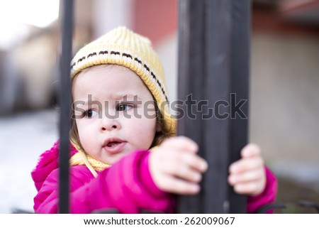 baby girl holding a metal gate in winter - stock photo