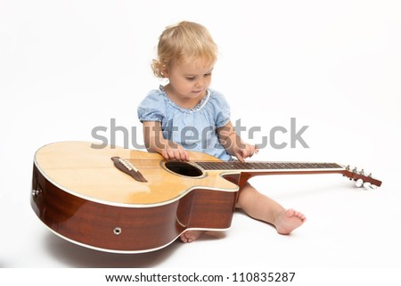 Baby girl holding an acoustic guitar - stock photo