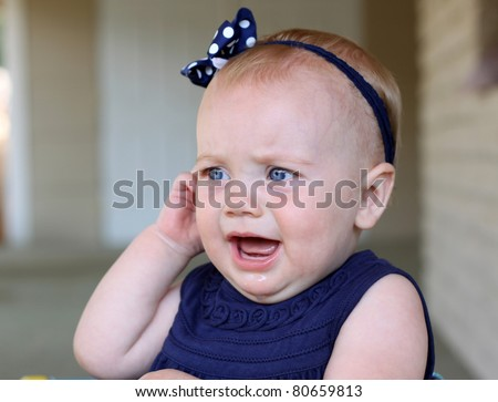 baby girl holding her ear in pain - stock photo