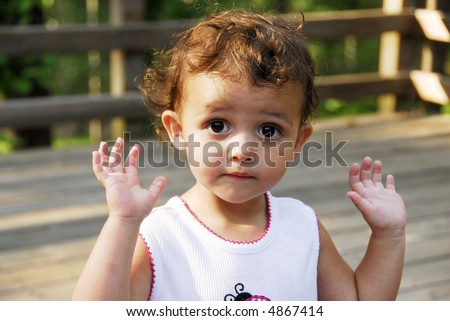 Baby girl holding her hands in the air. - stock photo