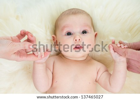 Baby girl holding parental hands. Top view. - stock photo