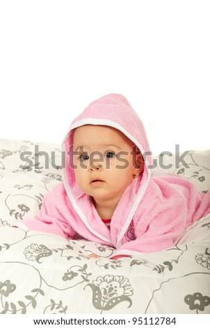 Baby girl in bathrobe lying on belly  in bed and looking at you with surprised face against white background - stock photo