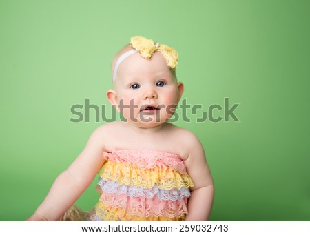 Baby girl in Easter outfit sitting, looking at the camera and smiling - stock photo