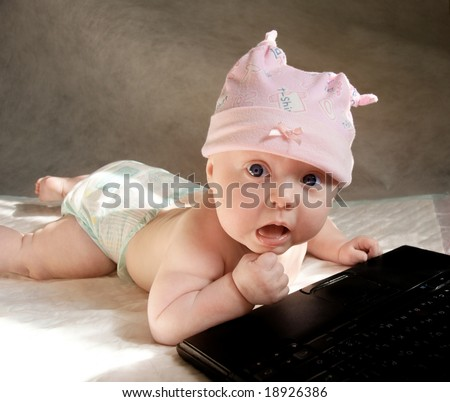 baby girl in funny pink bonnet playing with portable computer, her face with surprise expression - stock photo