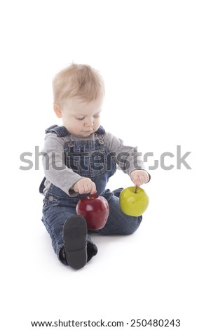 Baby girl in overalls choosing between red or green apple isolated on white - stock photo