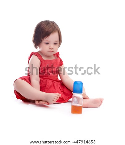 baby girl in red dress isolated on white background looking at a bottle of juice - stock photo
