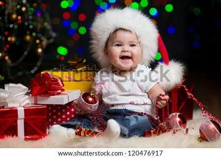 baby girl in Santa Claus hat with gifts under Christmas tree - stock photo