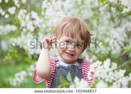baby girl in spring blossoming garden - stock photo