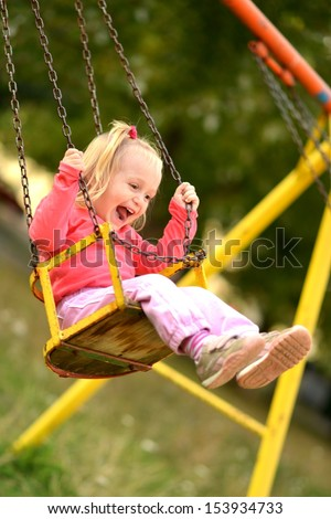 Baby girl in swing - stock photo