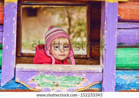baby girl in wooden house on the playground - stock photo