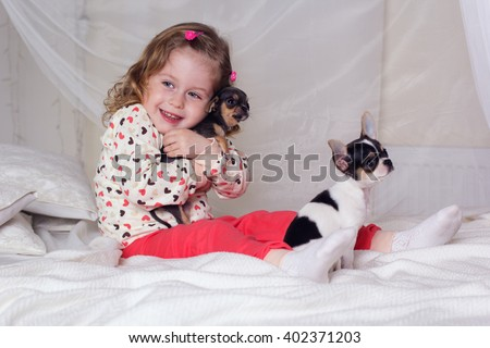 Baby girl is sitting on bed and hugging small dog - stock photo