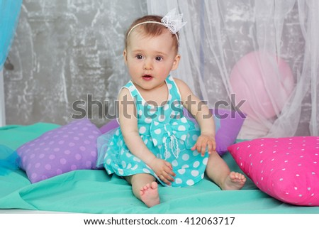 Baby girl is wearing nice dress sitting with pillows - stock photo