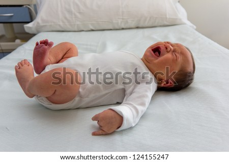 Baby girl just born crying laying on a hospital bed - stock photo
