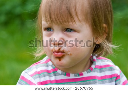 Baby-girl just finished her chocolate candy - stock photo