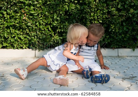 Baby girl kissing baby boy - stock photo