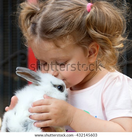 Baby girl kissing baby rabbit. Animal care concept. - stock photo