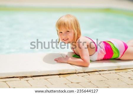 Baby girl laying near pool - stock photo