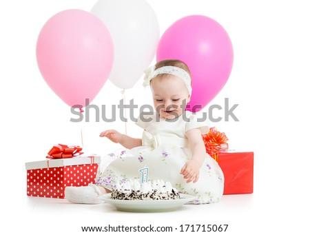 baby girl looking at birthday cake - stock photo