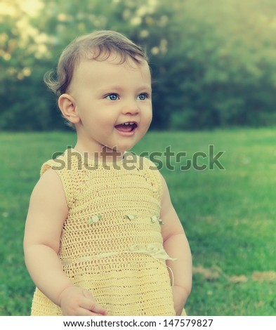Baby girl looking happy on green grass summer background. Closeup portrait - stock photo